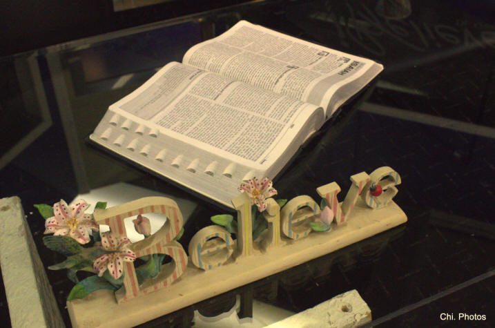 Display of an open Bible and scroll work 'Believe' on glass table at Dr. Gwen Ford's 'I Believe' TV studio.